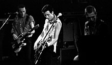 The rock band The Clash performing onstage. Three members are shown. All three have short hair. Two of the members are playing electric guitars.