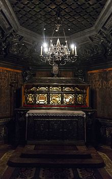 A coffin with glass sides allowing us to see the preserved body within, on a table inside an elaborately carved wooden nook, under a silver electric chandelier