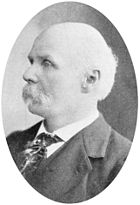 A black and white side profile portrait of an elderly man with a mustache, and wearing a suit and tie