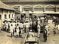 Crowd gathered around a sidewalk performer at a bus stop in Calcutta in 1945.jpg