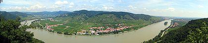 Un vasto fiume curva attraverso un paesaggio piatto.  Alla fine dell'alluvione 7pianura, montagne ripide si ergono sopra le case dai tetti rossi.