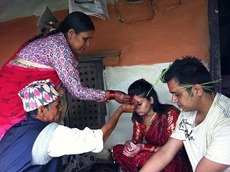 Dashain - Father and mother putting tika on their children's head during Dashain festival