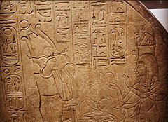 Rock stela covered in hieroglyphs and showing two standing figures, on the left the god Osiris, on the right a woman offering him incense.