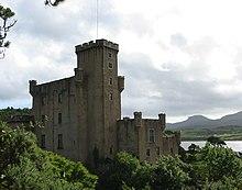 Un castillo gris con altas torres cuadradas se alza entre árboles llenos de hojas.
