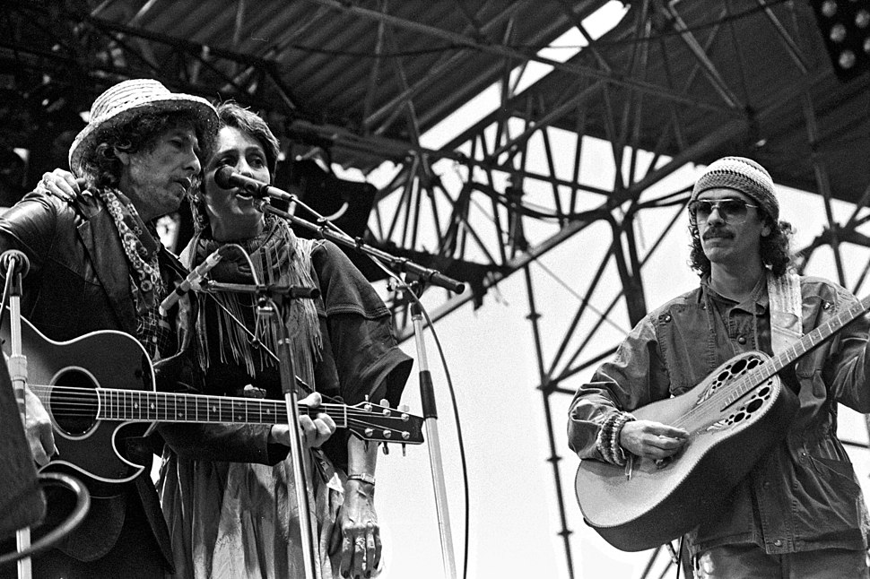 On stage outdoors, Dylan in a leather jacket and iconic porkpie hat & scarf, Baez wears a peasant skirt, sarape, tassled scarf around neck, her arm around Dylan's shoulder. Santana in workman's shirt & knit cap.