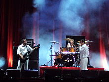 Three musicians dressed in white perform onstage—a drummer, a singer and a bass player