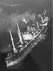 Black and white aerial photo of a merchant ship with splashes in the water along her port side. A monoplane aircraft is flying just above the ship.