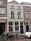 Huis met schilddak en geelgepleisterde lijstgevel waarin vensters met afgeronde bovenhoeken