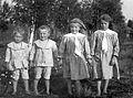 Gruppbild av fyra barn. Pojkar i randiga dräkter flickor i rutiga klänningar - Nordiska Museet - NMA.0054338.jpg