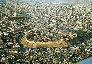 Citadel of Erbil - Hill with houses on top and surrounded by urban sprawl
