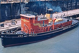 "Santa Fe Railroad Tugboats - The John R. Hayden tugboat at the Todd shipyard in Alameda, California where she was dieselized. She was built in 1945 for the War Department as Large Tug LT-830. The tug is painted in ""War Bonnet"" colors which were similar to the Santa Fe Super Chief diesel-electric locomotives"