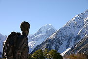 Dark statue with backpack facing a snow capped mountain