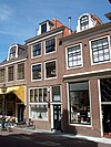 foto van Huis met eenvoudige gevel met twee verdiepingen waarin vensters met roedenverdeling. Pand wellicht ouder. Pui gemoderniseerd, deuromlijsting oud