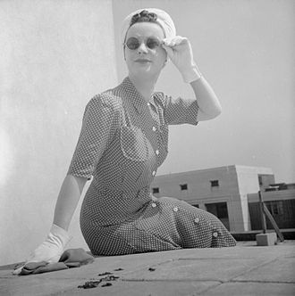 Art silk - A woman wearing a Utility rayon shirt dress with front-buttoning, 1943