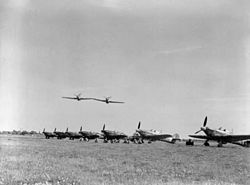 A photograph taken in 1942, of two Hawker Hurricane Mark IIs of No. 43 Squadron RAF, making a low level pass over the other aircraft of the Squadron that are lined up on the ground at RAF Tangmere, Sussex