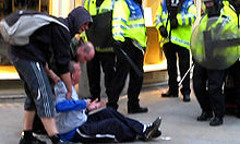 Tomlinson sitting on the ground facing the police with his arms outstretched; two men are helping him up