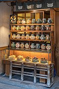 Illuminated wooden shelf with many glass jars containing cookies for sale in Tokyo.jpg