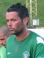 Head and shoulders of dark-haired white man wearing a green sports shirt