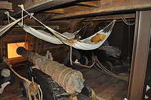 Photograph of a reconstructed ship's deck with large cannons with hammocks slung overhead
