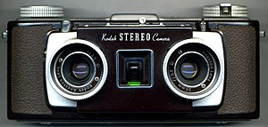 A Kodak Stereo Camera. Brown in color, it features two lenses, one next to the other, with a viewfinder between the two.
