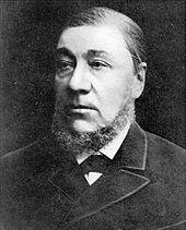 Mężczyzna około pięćdziesiątki w ciemnym garniturze i ciemną brodę z brodą