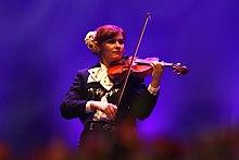 Mujer mariachi con atuendo moderno tocando el violín.
