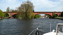 a red brick built bridge with shallow arches spanning a river, viewed from the front of a small boat