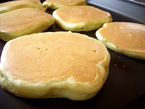 Pancakes being cooked on a griddle.