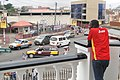 Man Watches Street Scene from Balcony of Barclay's Bank - Kumasi - Ghana (4756194208).jpg