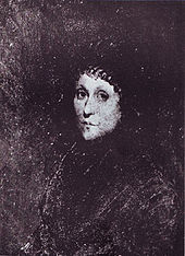 A young woman dressed in black with a black cap covering her hair