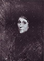 Une jeune femme vêtue de noir avec une casquette noire couvrant ses cheveux