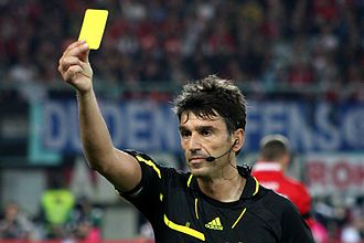 Bad call - A soccer/football referee displaying a yellow card against a player