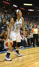 "full height portrait of a young woman with long dark hair pulled back, wearing uniform that says ""Lynx 23"""