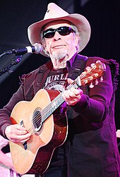 An old man in a cowboy hat, dark glasses and a dark jacket playing a guitar on stage