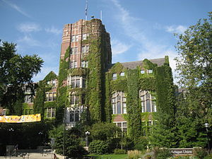 Red brick building with large windows, tall central tower, and green ivy growing on the facade