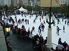 An ice skating rink with dozens of skaters