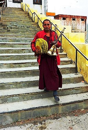History of primitive and non-Western trumpets - Monk with trumpets and hats. Key Monastery Spiti, Himachal Pradesh, India