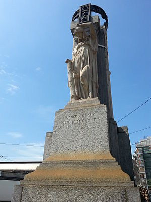 War Memorial of Musocco - East: Italy statue with the written Musocco ai suoi gloriosi caduti on the marble