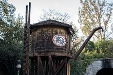 A wooden water tower with the DRR's three-letter logo painted on the side