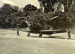 Single-engined military monoplane with propeller spinning, on jungle airfield