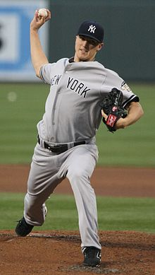 "A man in a grey jersey, which says ""New York"" across the front, throws a baseball."