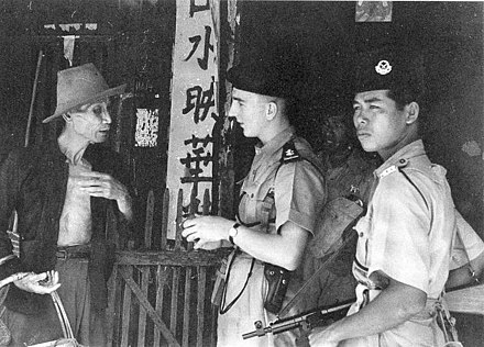 Police officers question a civilian during the Malayan Emergency. Police in Malayan Emergency.jpg