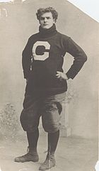 Large young man in a turtleneck and football pants, with hands on hips.