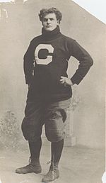 Large young man in a turtleneck and football pants, with hands on hips