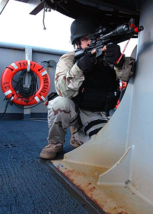Prevail (IX-537) - A sailor provides cover during a simulation aboard the training support vessel Prevail. Prevail offers a training environment for VBSS teams to test their maritime security operations skills.