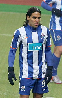 Man with long dark hair held with a headband, wearing a football kit composed of a shirt with vertical blue-and-white stripes and blue shorts. He also wears a blue sleeved undershirt and winter gloves.