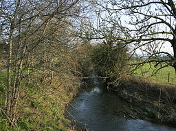 a narrow stretch of river, surrounded by trees on banks either side, sunny day, some clouds