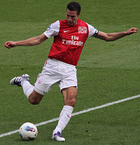Robin van Persie, wearing a red and white football jersey and white shorts, prepares to kick a football with his right foot with both arms outstretched.