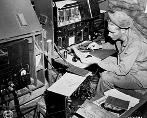 Signal Corps (United States Army) - Radio operator Cpl. John Robbins, 41st Signal, 41st Infantry Division, operating his SCR 188 in a sandbagged hut at Station NYU. Dobodura, New Guinea on 9 May 1943.
