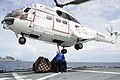 Sailor extends a hook toward a SA-33J Puma helicopter on the flight deck of USS Curtis Wilbur. (27879102582).jpg
